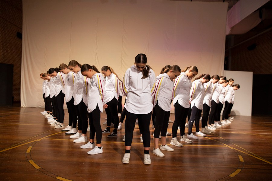 Group of students on stage dressed in black pants and white shirts in v formation during Dance Showcase
