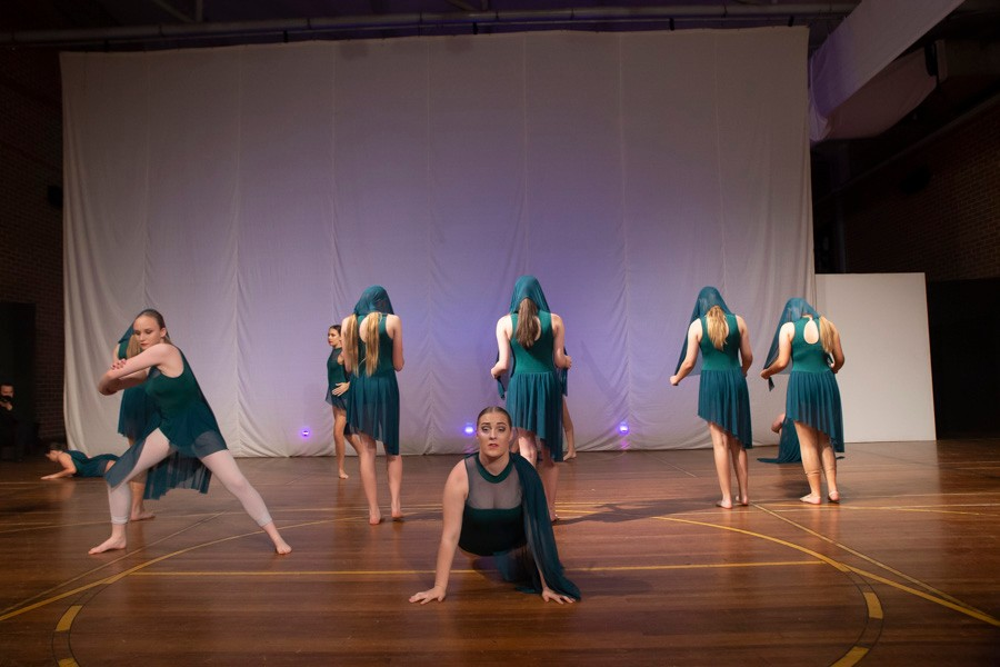 Group of female dancers dressed in aqua costumes on stage
