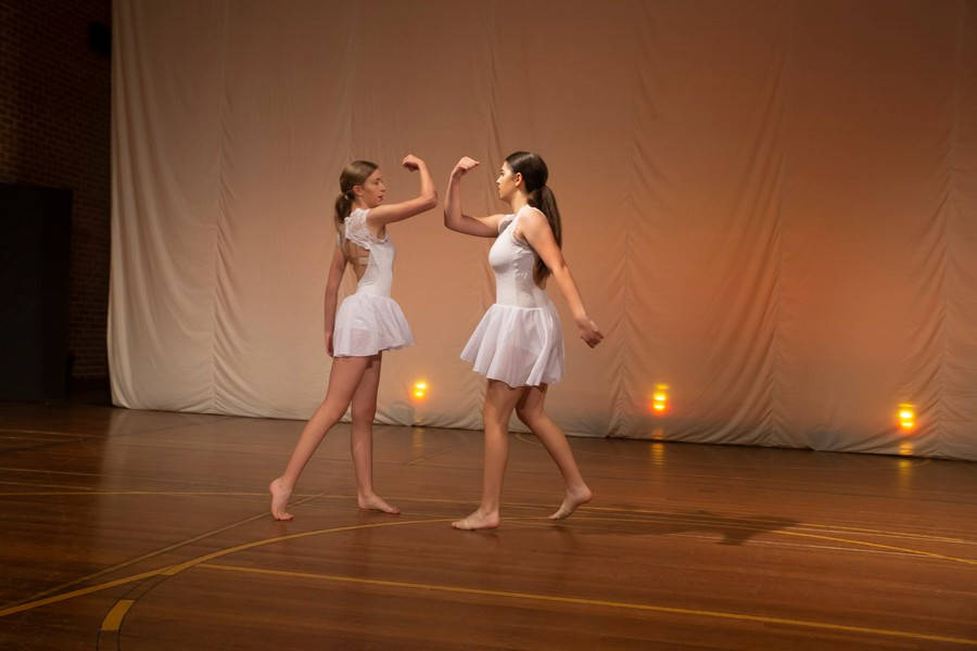 2 female dancers dressed in white on stage