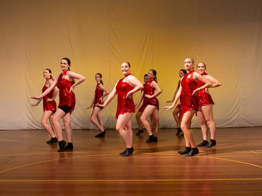 Female students dressed in red with black shoes dancing on stage