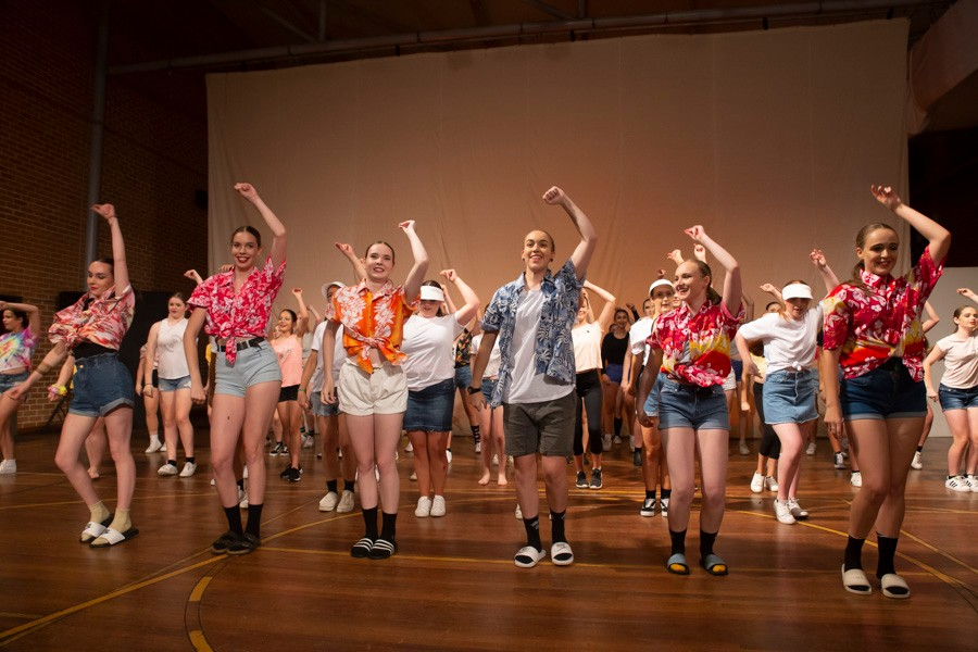 Group of male and female dancers with one arm raised on stage dressed in colourful shorts and shirts