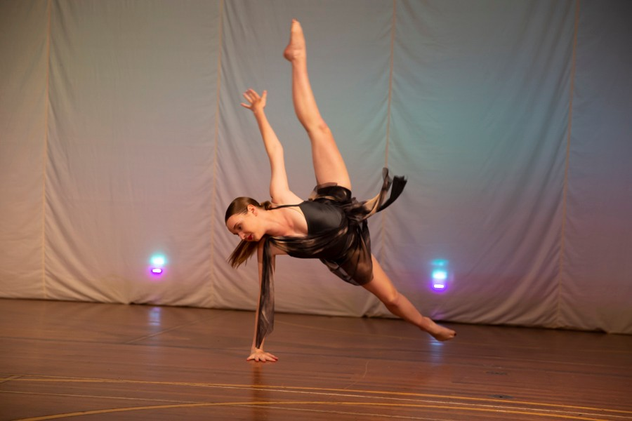 Solo female dancer on stage with one arm and one leg in the air and one arm and one leg on the ground