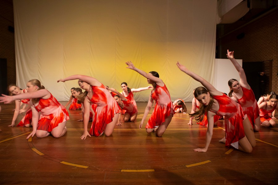 Group of female dancers in red costumes kneeling on floor with one arm raised