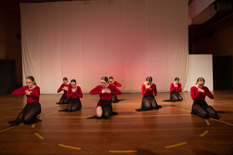 Group of female dancers in red and black costumes kneeling on floor