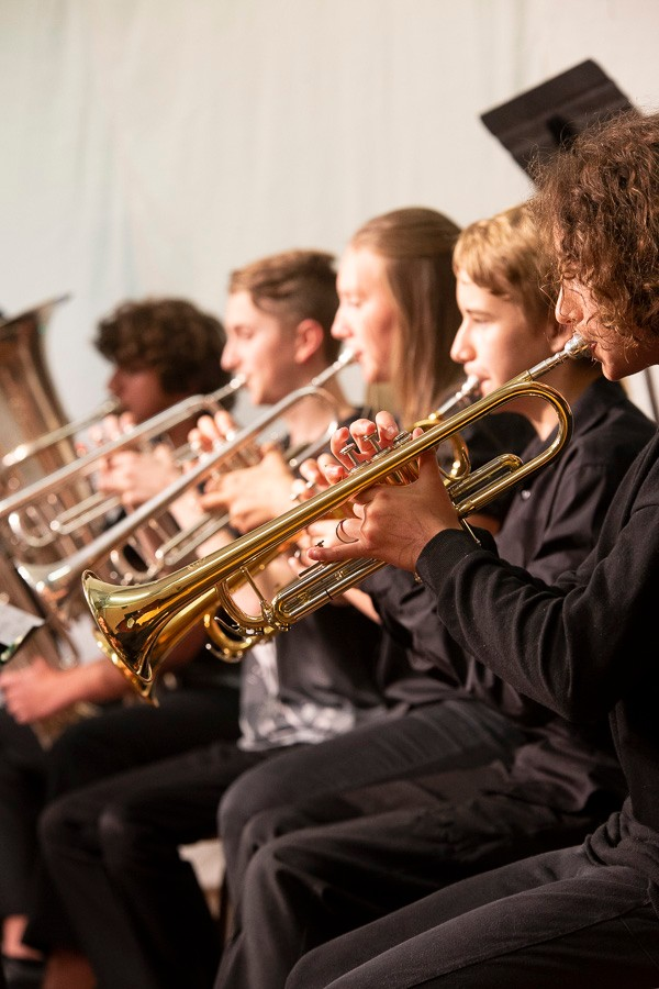 Group of students wearing black playing brass instruments