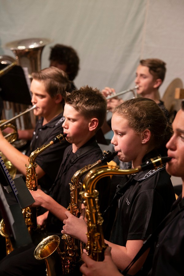 Group of students wearing black and playing brass instruments