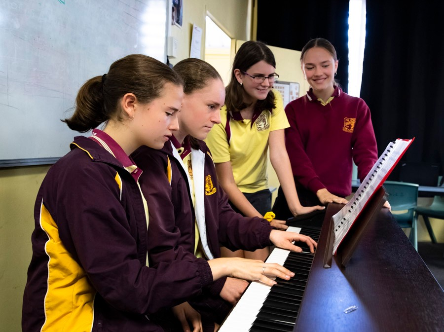 Group of female students clustered around a piano
