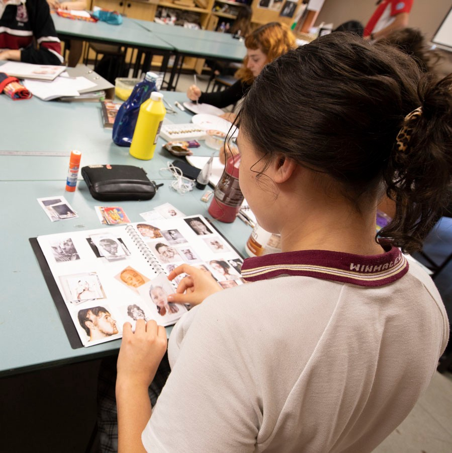 Rear view of female student in Visual Arts class working in her book