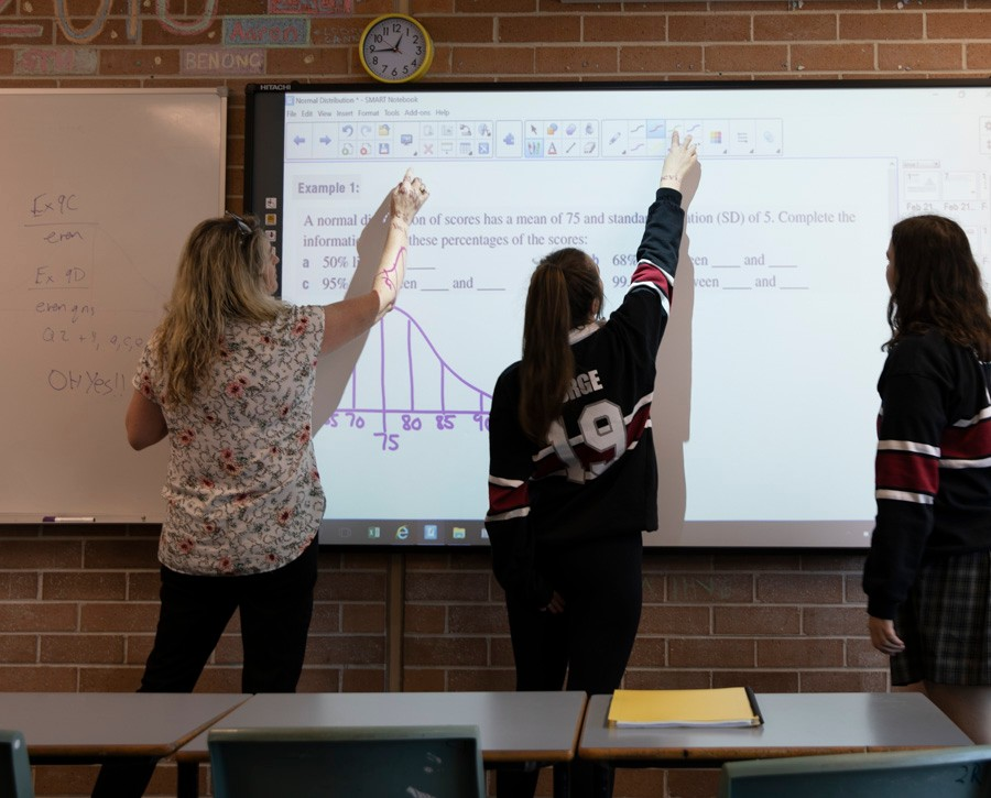 Female teacher and two female students working on interactive whiteboard.