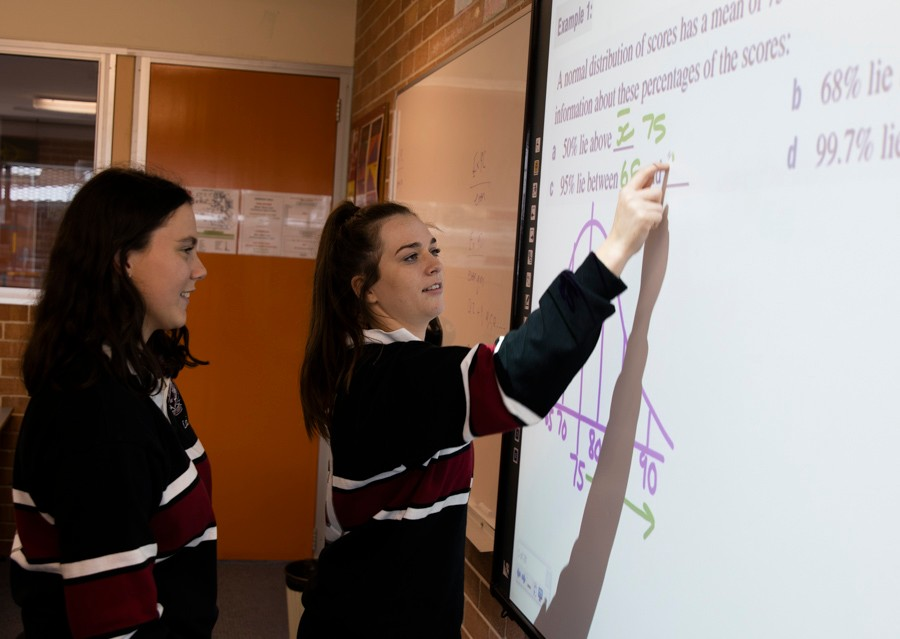 Two female students working on interactive whiteboard
