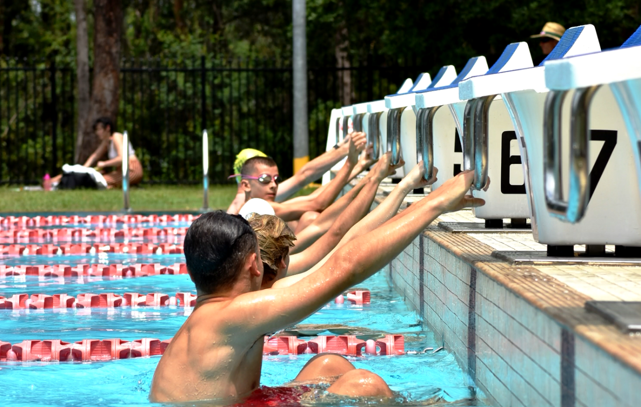 Swimmers in pool lined up at the start of a backstroke race