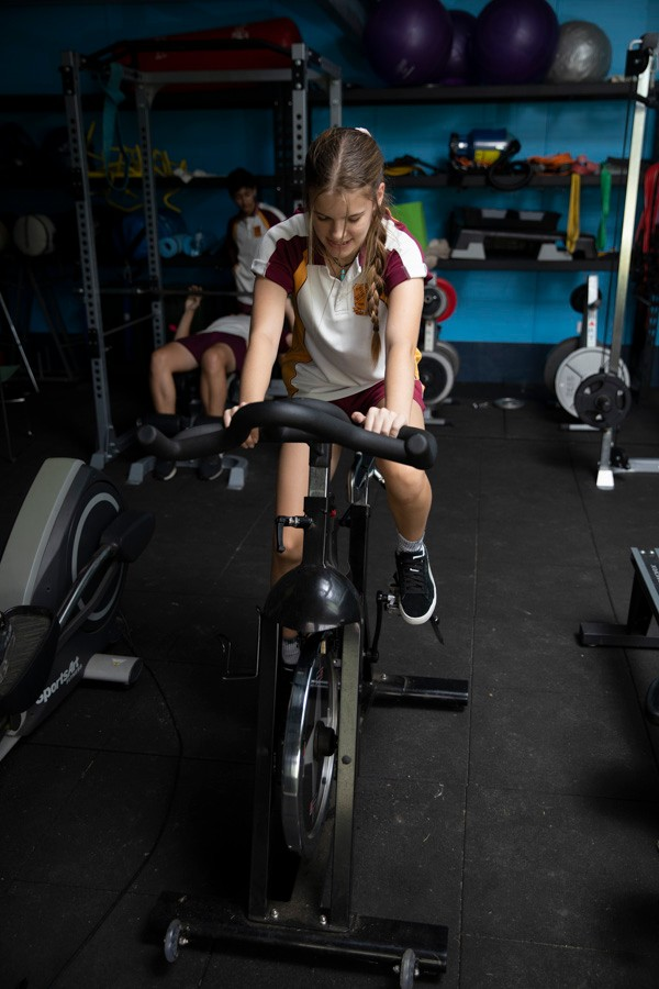 Female student in sport uniform on exercise bike in gym