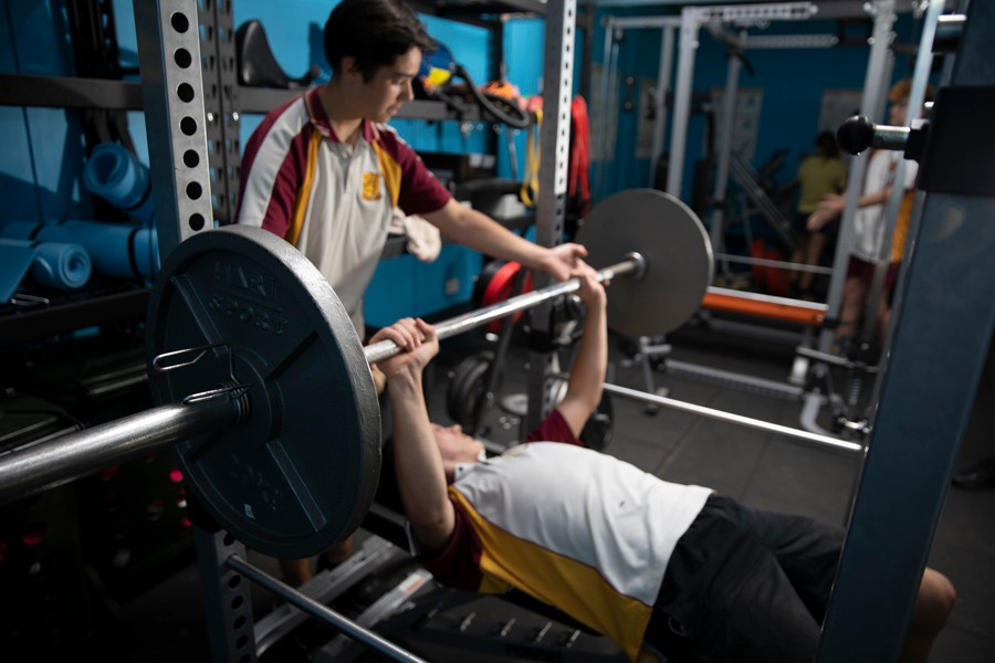 Two students in the gym, one lying down with hands underneath barbell and another student assisting