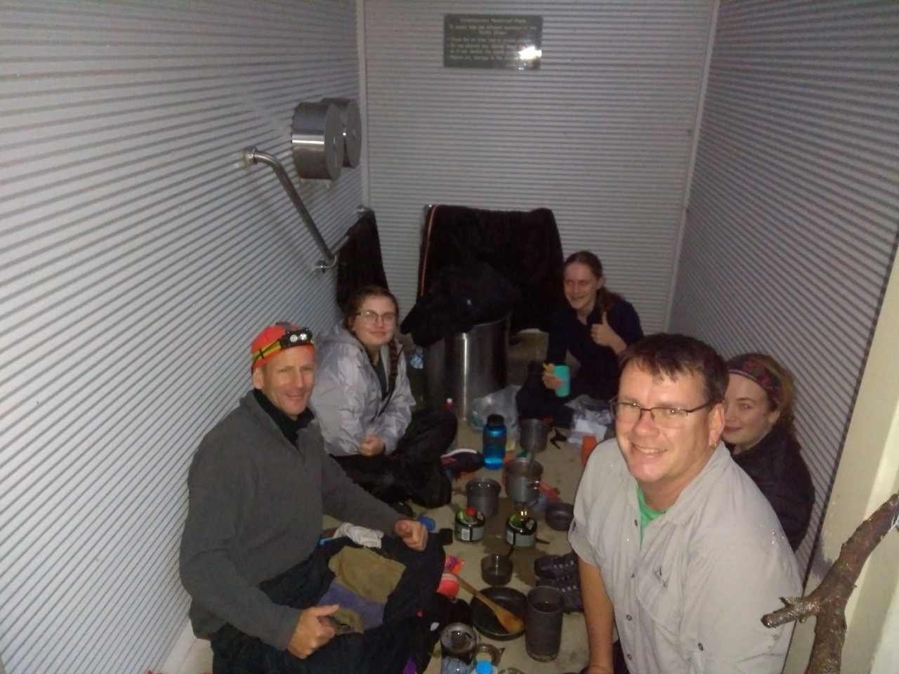 Staff and students sitting in cabin with eating utensils on Duke of Edinburgh snow trip