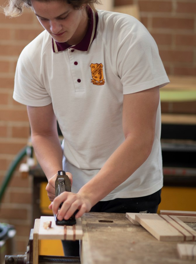 Male student using tool on wood