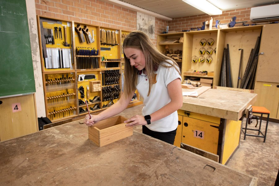 Female student working on wooden box