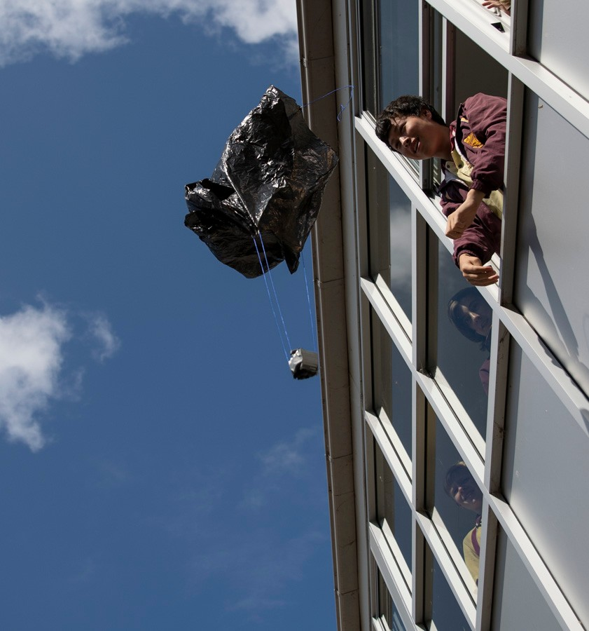 Student watching weight with plastic bag balloon attached descend to the ground from a window