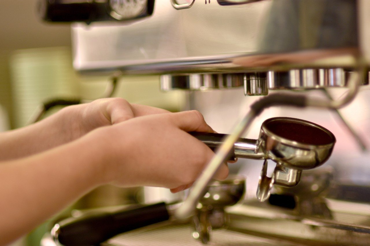 Close up of industrial coffee machine with two hands holding a group handle filled with ground coffee