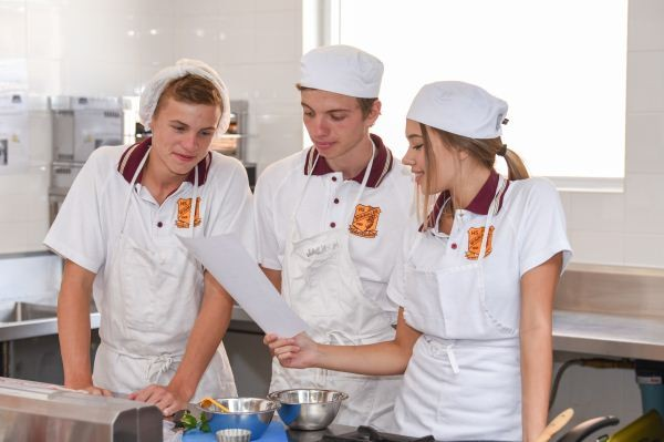 Three students in white aprons and caps over their school uniform in a Hospitality class