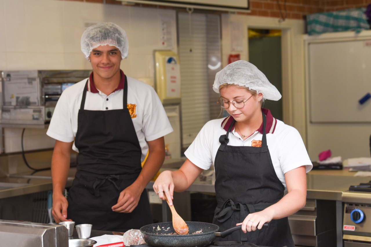 A male and female student in aprons and caps over their school uniform in a Hospitality class. The female student is looking down at a frypan and is stirring with a wooden spoon.
